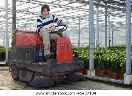 A man on an industrial cleaning machine, cleaning the concrete floor of a glasshouse - stock photo