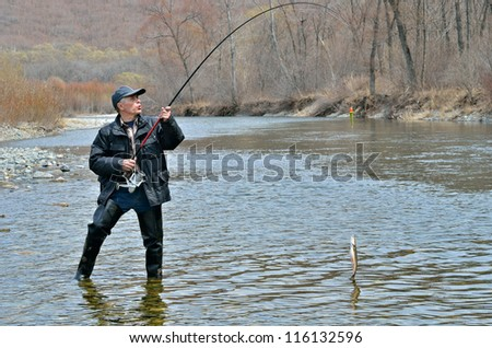 A man on fishing with fish on hook.