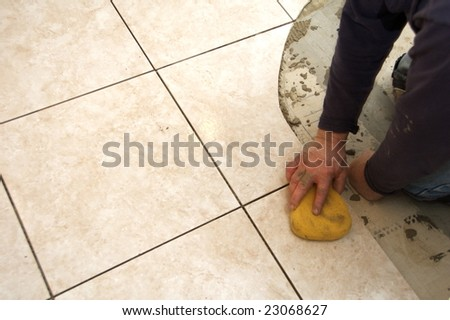 A man on his knees installing a ceramic tile floor - stock photo