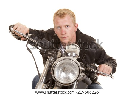 A man on his motorbike leaning over the handle bars. - stock photo