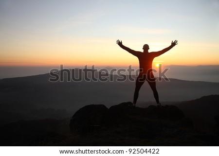 A man on the mountain peak - stock photo