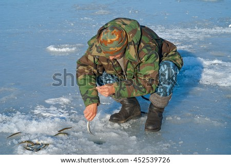 A man on winter fishing on ice of river. Season of smelt fishing. - stock photo