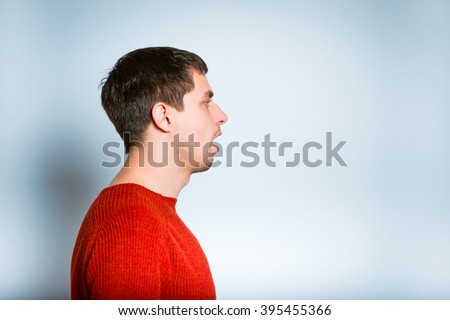 a man opens his mouth in profile, isolated on a gray background - stock photo