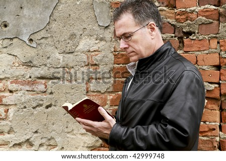 A man outside leaning up against and old brick wall reading a small New Testament bible.