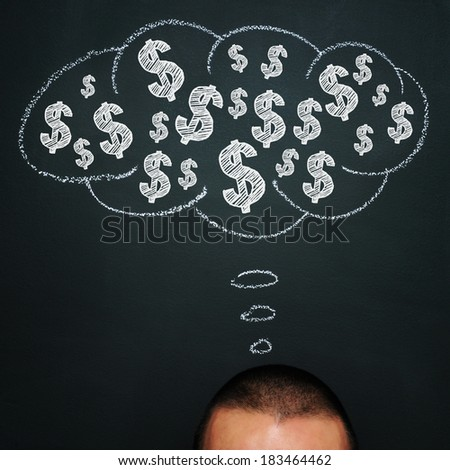 a man over a blackboard with a thought bubble drawn in it and a pile of dollar signs in it - stock photo