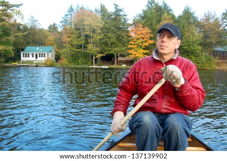A man paddles a canoe on a lake in Vermont during fall foliage season. Summer cabins line the shore in the background. - stock photo
