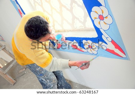 a man painting colorful frame of a window