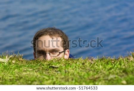 A man peeking on a green riverside - stock photo