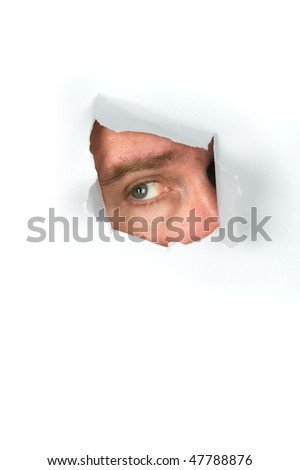 A man peers through a torn paper hole. - stock photo