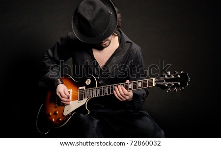 A man playing electric guitar in black clothes