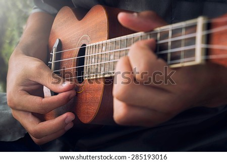 A man playing ukulele in close up view. - stock photo