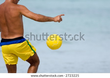 A man playing with a yellow ball on the beach