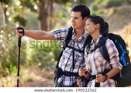 A man pointing something out to his girlfriend on the hiking trail - stock photo