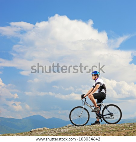 A man posing with a mountain bike on a ridge in Macedonia - stock photo