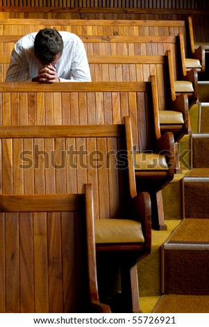 A man praying in church - stock photo