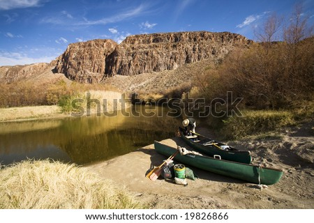 A man prepares a canoe to go down the Rio Grande near Terlingua, Texas.  The person is standing in the United States, while Mexico is the other side of the river. - stock photo