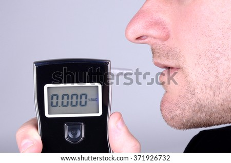 a man prepares to take a breathalyser test - stock photo