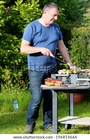 A man preparing delicious assorted meat and vegetables on barbecue grill for summer family party dinner
