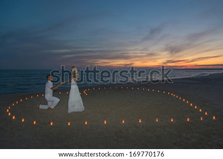 A man propose marriage to woman in candles heart at sea beach against sunset- St.Valentines Day romantic concept - stock photo