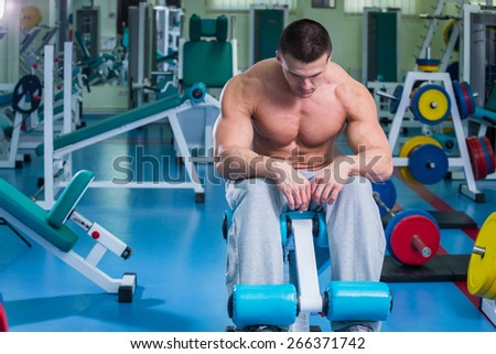 A man pumping abdominal muscles. Man in the gym. Man makes exercises. Sport, power, dumbbells, tension, exercise - the concept of a healthy lifestyle. Article about fitness and sports. - stock photo