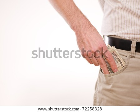 A man putting american money in his pants pocket - stock photo