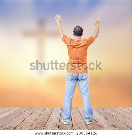 A man raising hands on wooden paving over the cross on a sunset. Thanksgiving, Christmas, Worship, Forgiveness, Mercy, Repentance, Adoration, Glorify, Humble, Love concept - stock photo