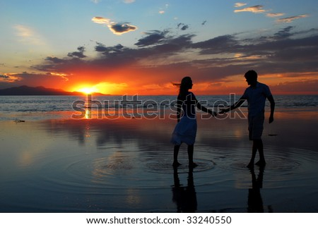 A man reaches for a woman's hand during a sunset. - stock photo