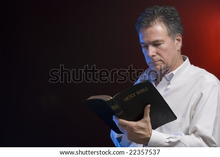 A man reading a bible, background and side lighting with red and blue gels. - stock photo