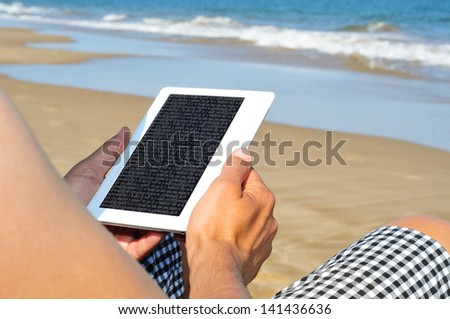 a man reading on an e-book on the beach - stock photo