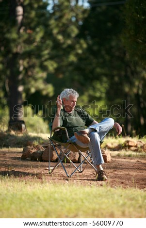 a man relaxes outside as he does a crossword puzzle and communes with nature - stock photo