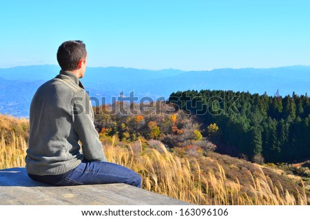 A man relaxing and enjoying a view of the mountains with copy space. - stock photo