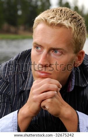 A man relaxing near a mountain lake - stock photo