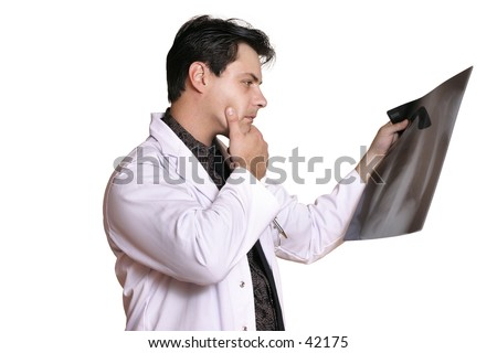 A man reviews patient x-ray looking for signs of disease, tumour, fracture, etc
