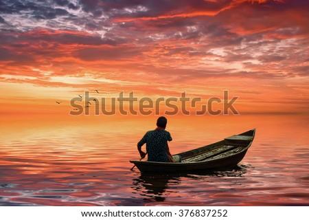 A man riding boat in bangladesh - stock photo