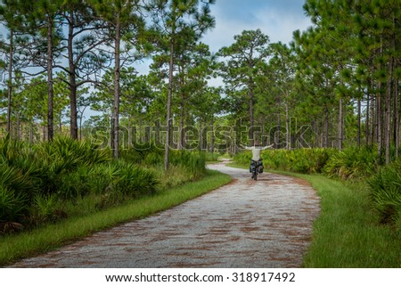 A man riding his bicycle on a path in Florida - stock photo