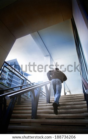 A man running up steps in a city. Chasing or being chased. - stock photo