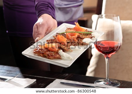 A man?s hand holding a white tray with crispy potato pancakes decorated with salmon and sour cream