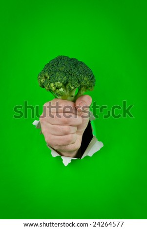 A man's hand holding green broccoli.