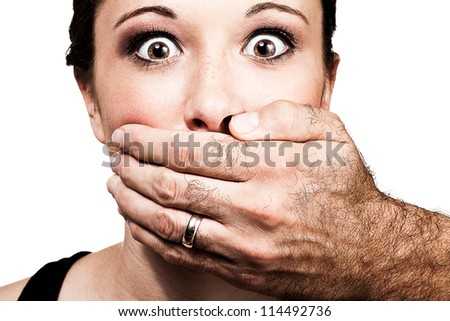 A man's hand holds a young woman's face, prefenting her from speaking as she stars into the camera in horror. - stock photo