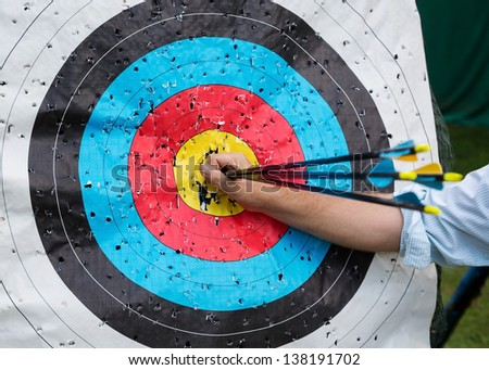 A man's hand pulls arrows from hitting 10 points. Standard colorful target for archery. - stock photo