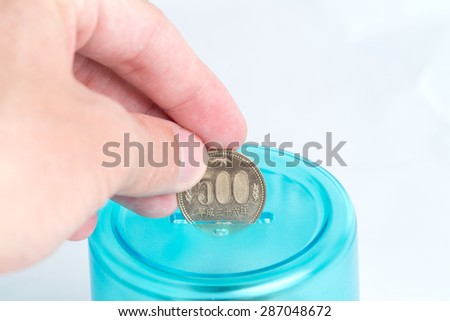 A man's hand putting a 500 Japanese Yen coin into a blue bank with a white background.