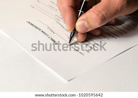 A man's hand signs a family loan agreement.