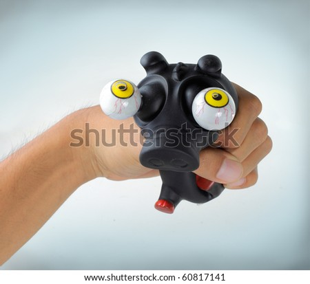 a man's hand squeeze a little black funny pig - stock photo