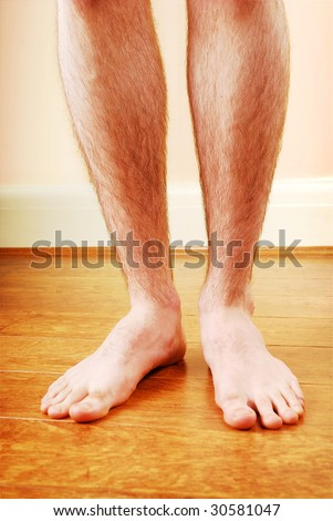 A man's naked legs standing on a bath mat.