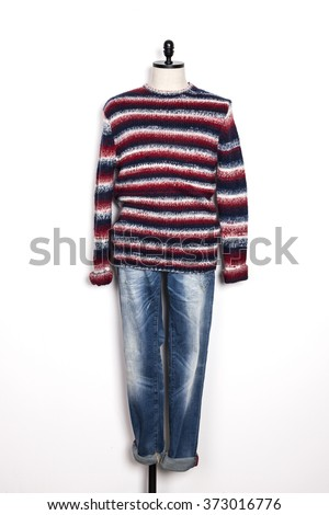 A man's red sweater with stripes and blue denim(jeans, trousers) with mannequin on the wall isolated white.  - stock photo