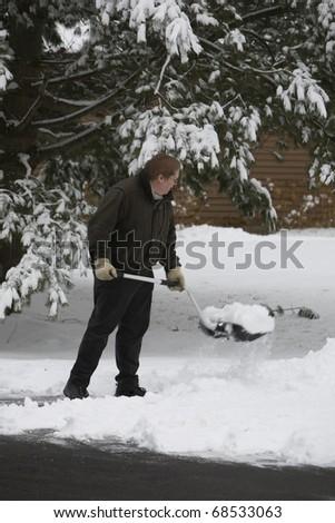 A man shovels snow - stock photo