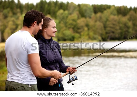 A man showing a woman how to fish - stock photo