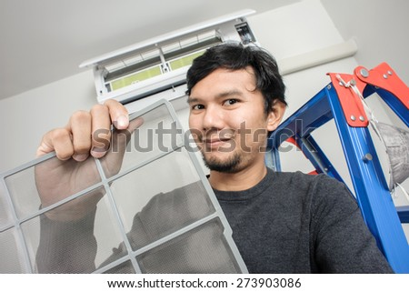 a man showing clean air filter after cleaning (focus on the filter) - stock photo