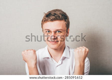 A man shows the victory with his fists up. On a gray background. - stock photo
