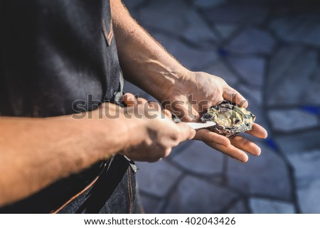 A man shucking an oyster and preparing them to be cooked. - stock photo